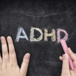 Child writing ADHD on blackboard for ADHD Awareness Month