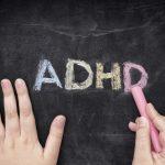 Child writing ADHD on blackboard for ADHD Awareness Month