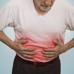 Stomach ache, man placing hands on the abdomen, constipation