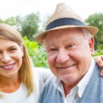 Elderly man smiling with woman next to him