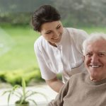 Elderly man smiling next to carer