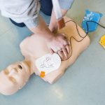 Person practicing chest compressions on dummy.